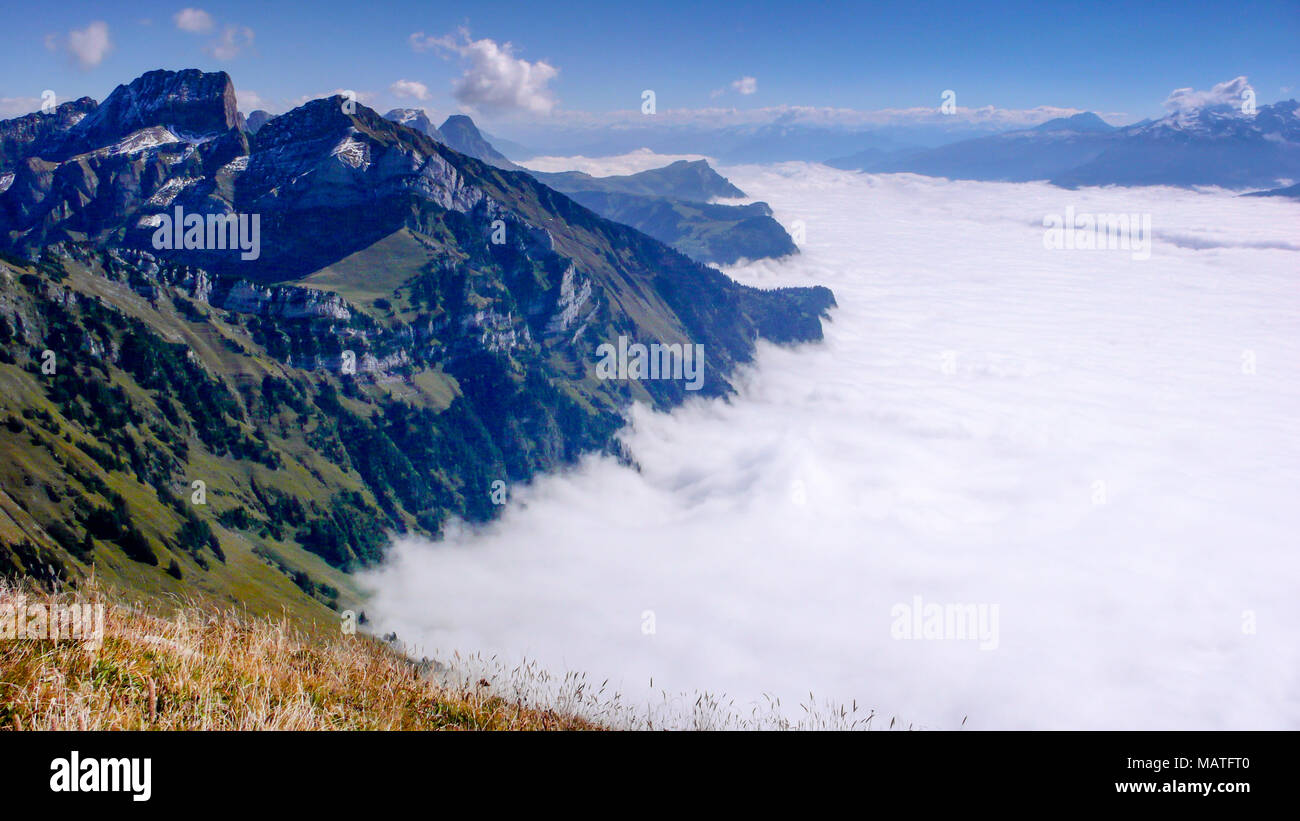 mountain landscape on a beautiful summer day with thick cloud cover in the valleys far below - Stock Image
