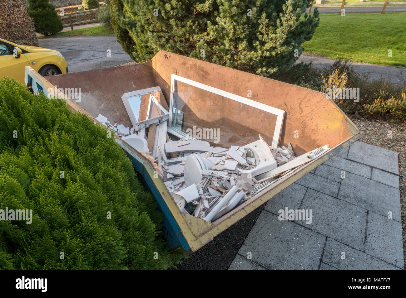 Rubbish skip on the driveway of a house, full of rubble from renovating a bathroom - Stock Image
