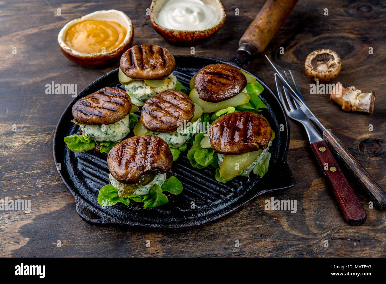 Grilled portobello bun mushroom burgers on cast iron grill pan ob wooden background, top view. Stock Photo