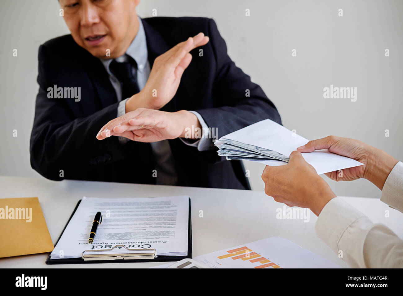 Businessman refusing money in the envelope to agreement contract, Bribe and corruption concept - Stock Image
