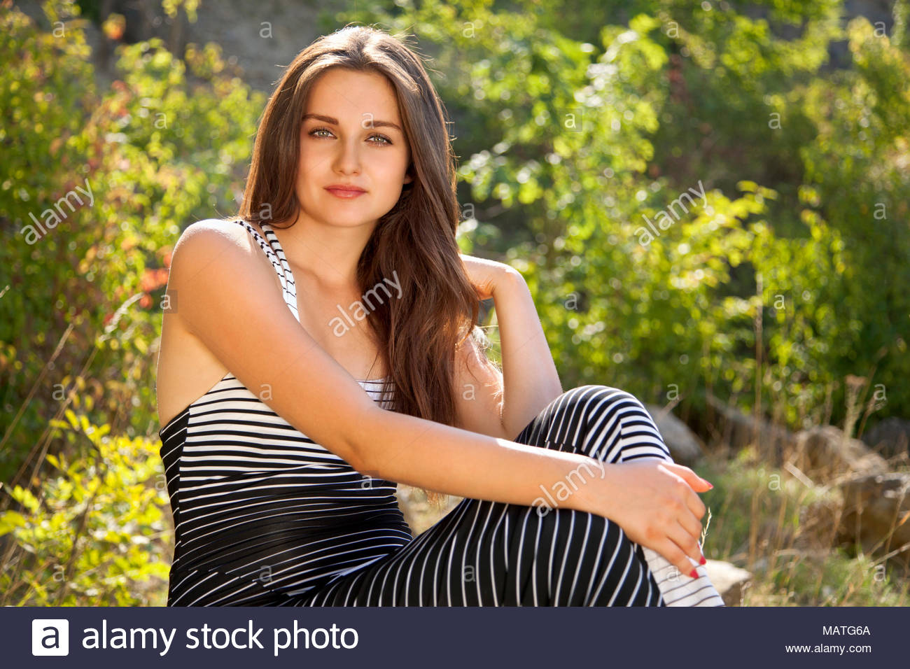 Young woman brunette, 20 years old, in front of blur green nature background looking at the camera. Shines the bright sun. - Stock Image