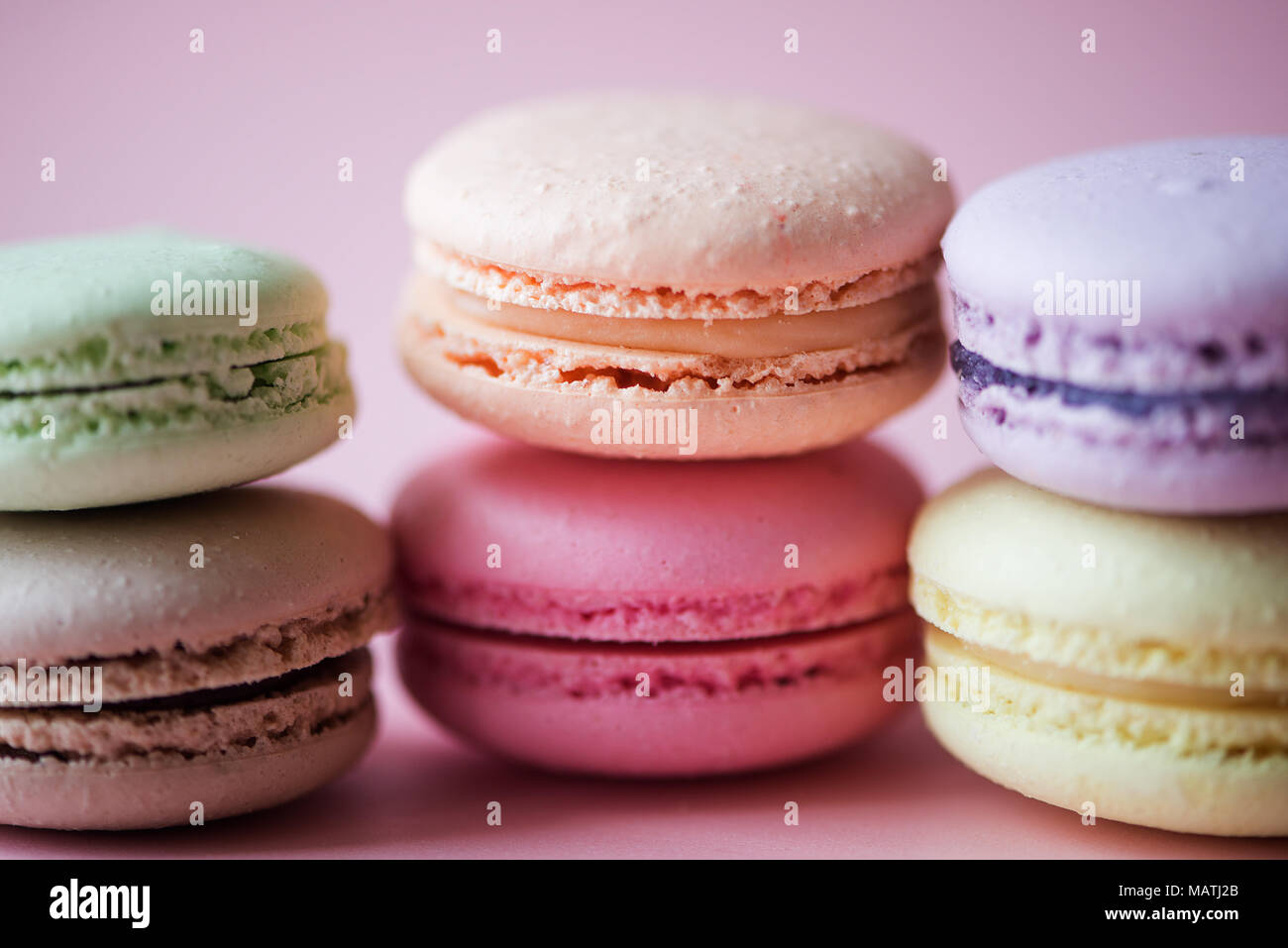 Sweet French macaroons cake (or macarons) with vintage pastel colored tone on pink background. - Stock Image