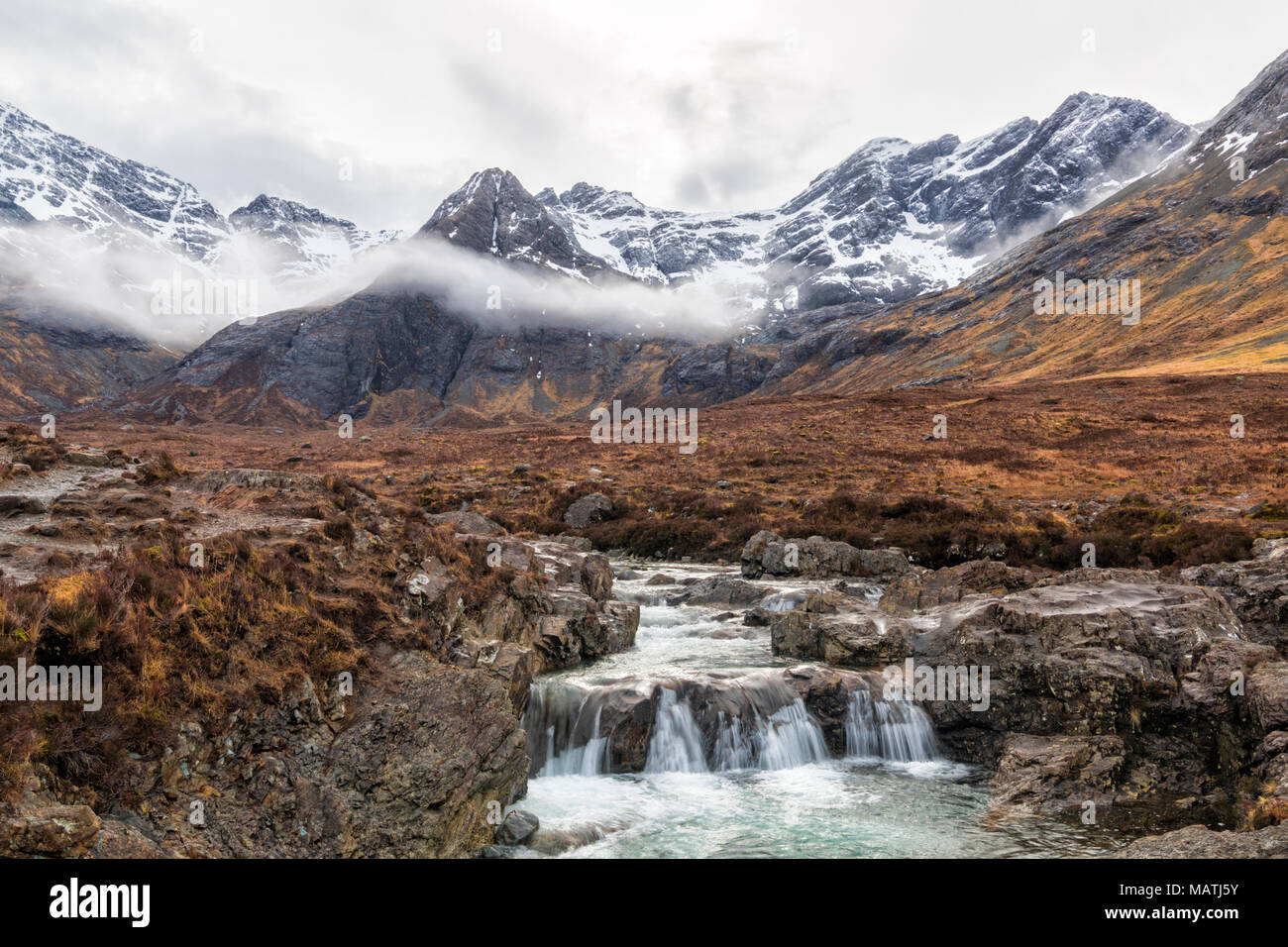 Fairy Pools with mist over the Black Cuillin mountains with waterfalls at the river Brittle, Isle of Skye, Scotland, UK in March - Stock Image