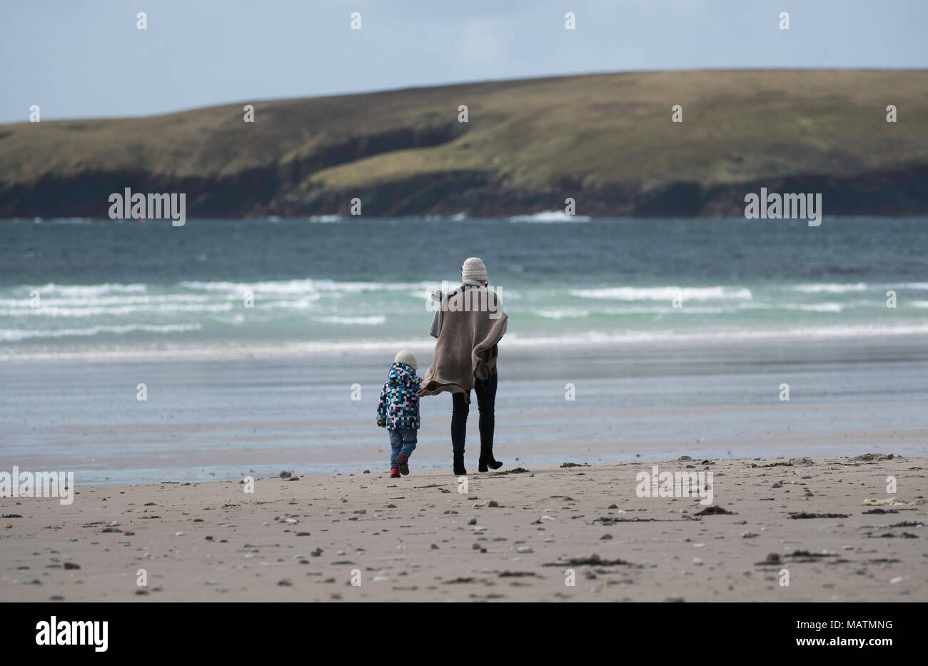 Mother and young son strolling, walking on beach during windy weather, Warm Clothes and Woollen White Hats, Cliffs and Green Island in the background Stock Photo