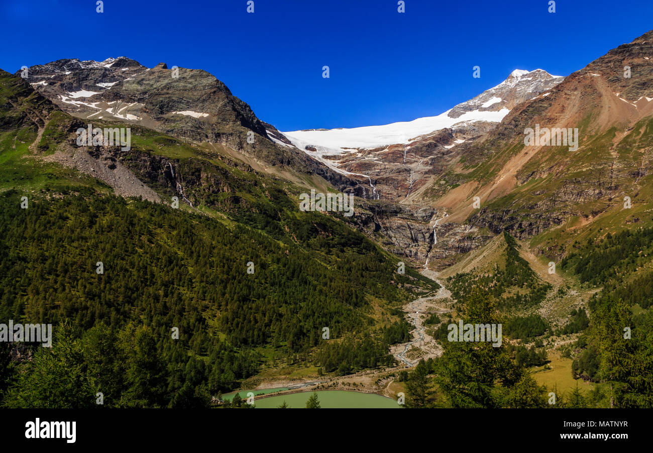 view on snowcapped mountains in the Bernina Range on the border of Switzerland and Italy from railway station Alp Grum, near St. Moritz, in summer. Gr - Stock Image