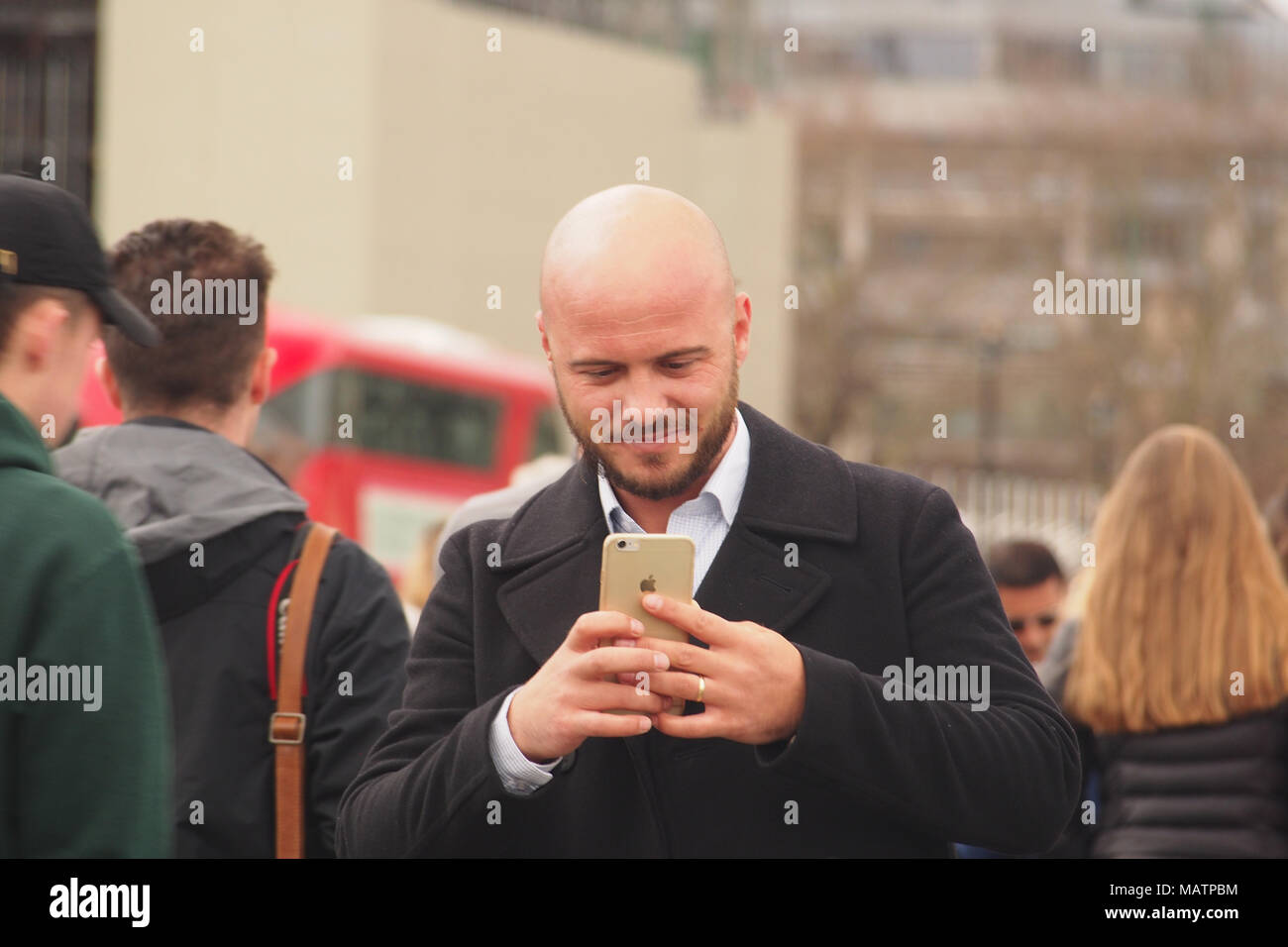A man wearing an overcoat taking a photograph on his smartphone in London among a crowd of pedestrians and with a bus in the background - Stock Image