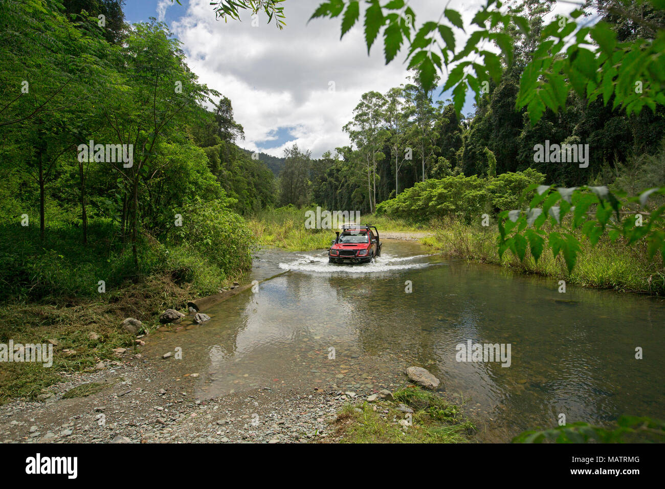 Red four wheel drive vehicle crossing creek hemmed with emerald forests in Conondale Ranges National Park Queensland Australia - Stock Image