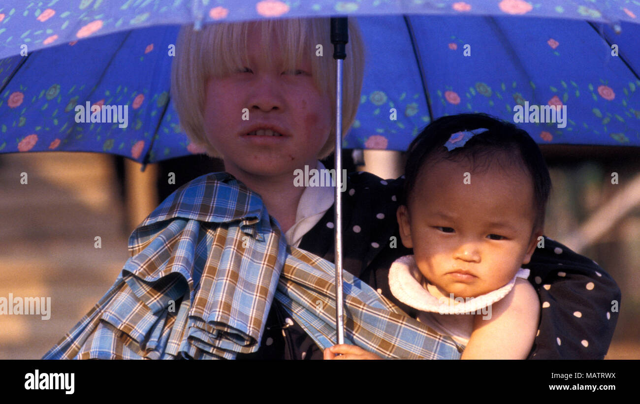 An indigenous albino girl from Burma's remote An tribe protects herself and her sister from the hot sun with a parasol. - Stock Image