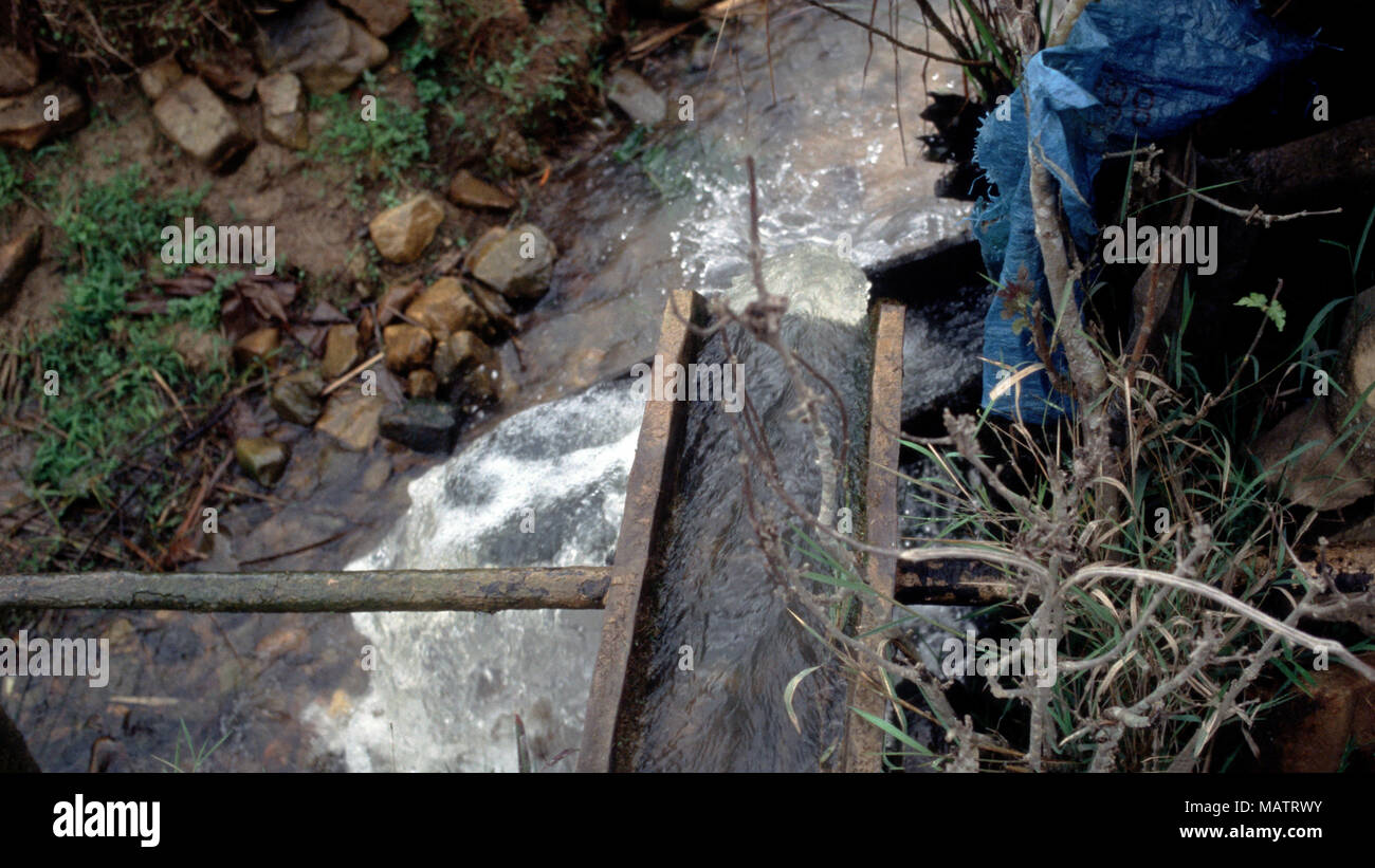 In a H'mong (Hmong) village near Sa Pa, Vietnam, flowing stream water, wooden pipes and gravity are used as a clean, sustainable energy source. - Stock Image