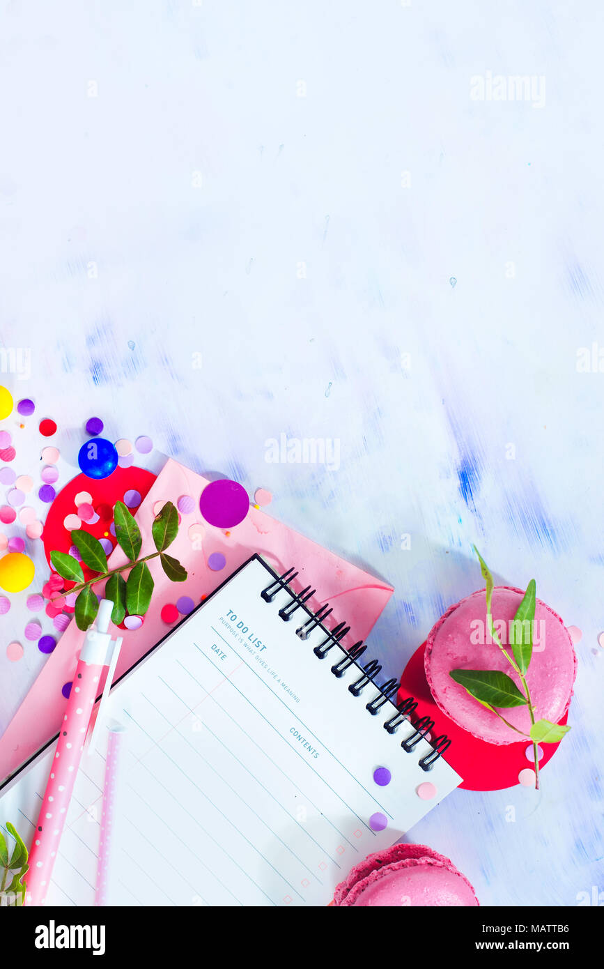 Party management and organization concept with sweets, confetti and an open notepad with blank pages. Creative celebration flat lay with copy space. - Stock Image