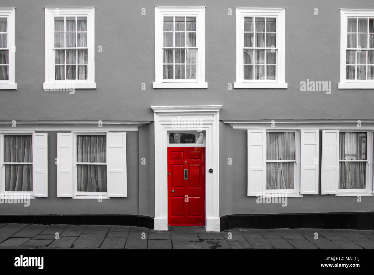 A facade of a traditional village house in Great Britain. Its red door are isolated in a black and white picture. - Stock Image