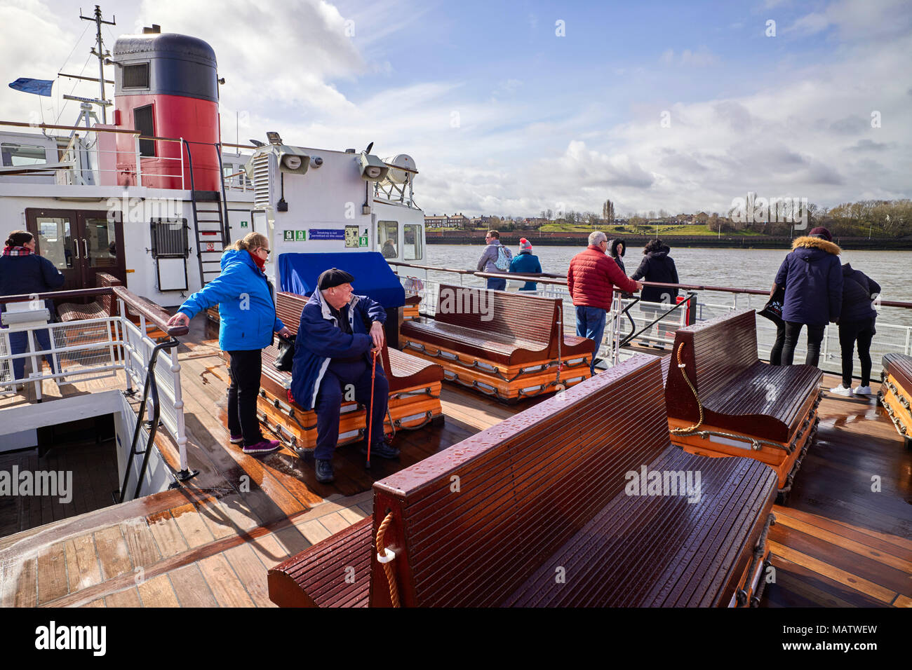 Passengers on the outside deck of the Royal Iris ferry crossing the river Mersey - Stock Image