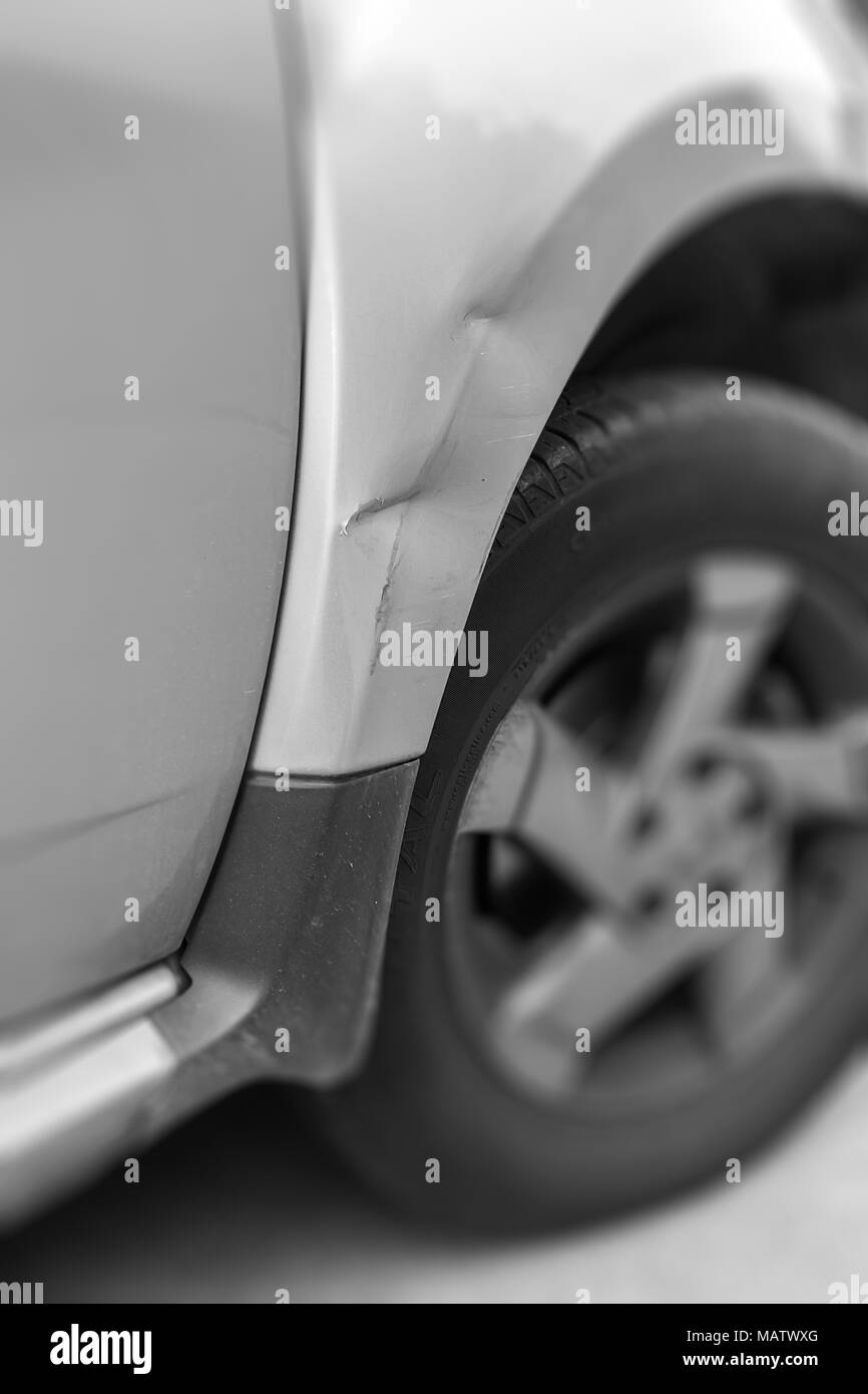 Dents on the car caused by the accident. Shallow depth of field. Stock Photo