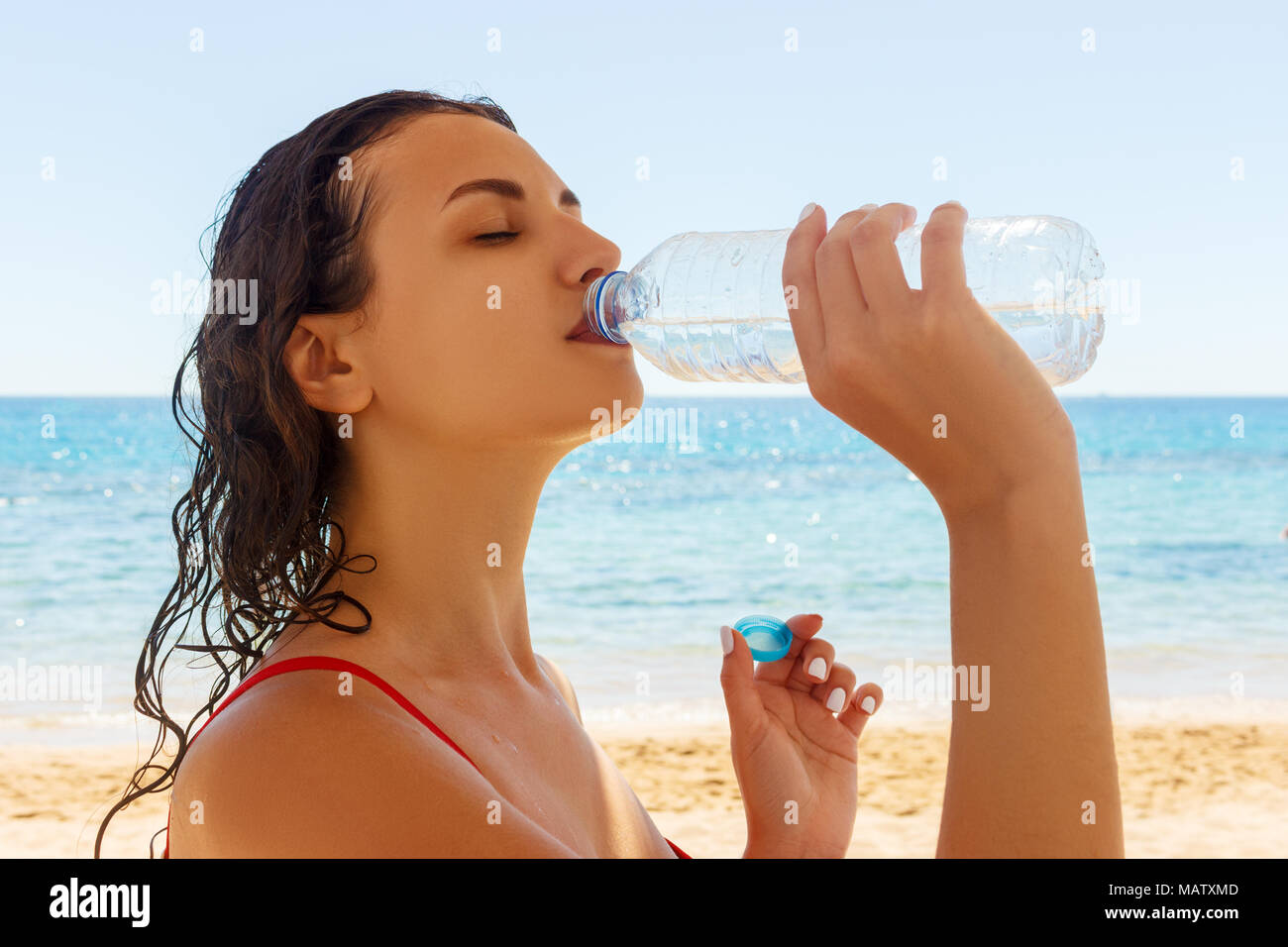 Young woman in a red swimsuit, drinking sparkling water from a transparent bottle on the beach. - Stock Image