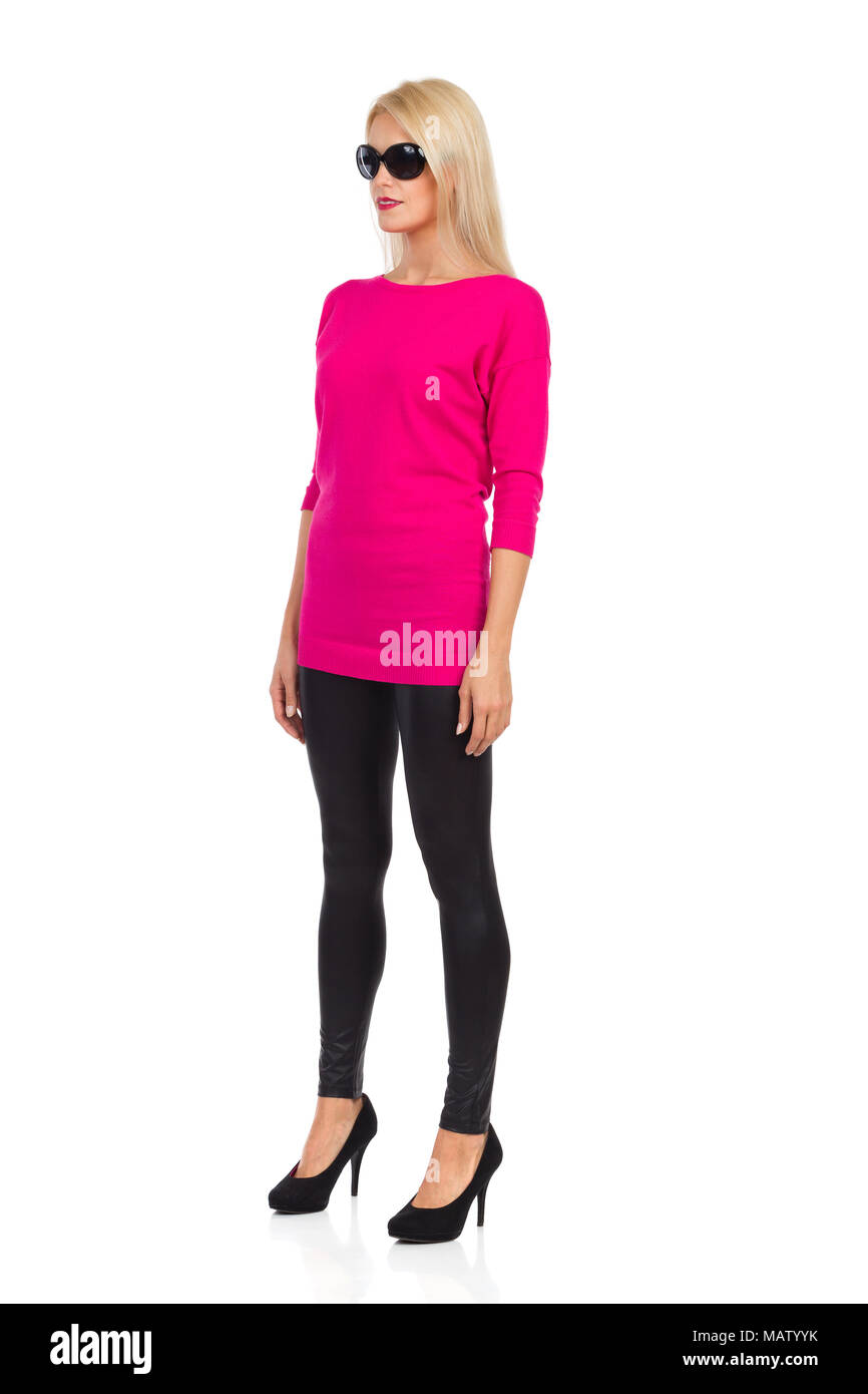 Serious beautiful blond woman in sunglasses, black leggings, high heels and pink sweater is standing at attention and looking away. Front side view. F - Stock Image