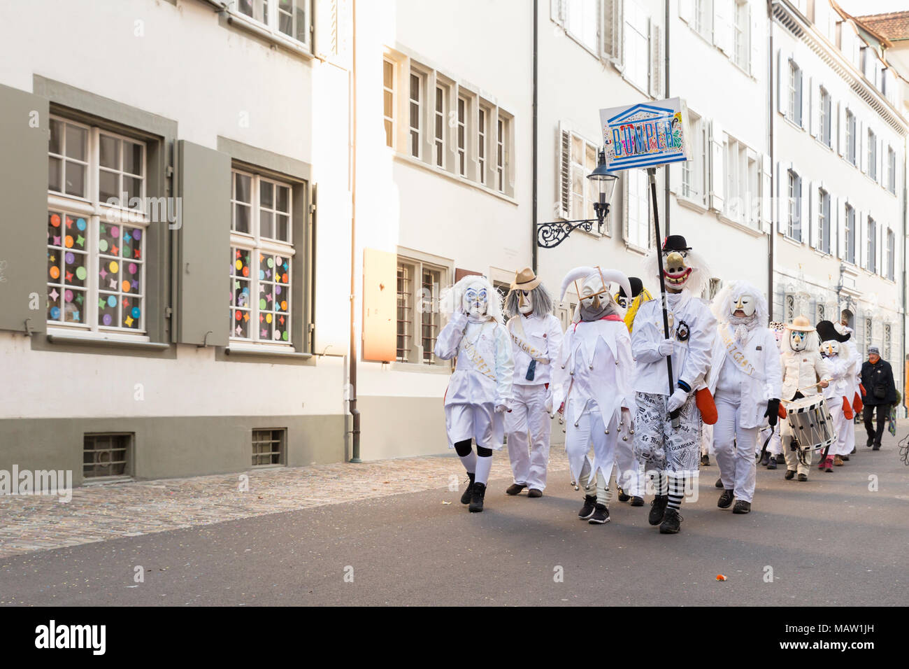 Basel carnival. Augustinergasse, Basel, Switzerland - February 21st, 2018. Carnival group in white costumes in the old town - Stock Image