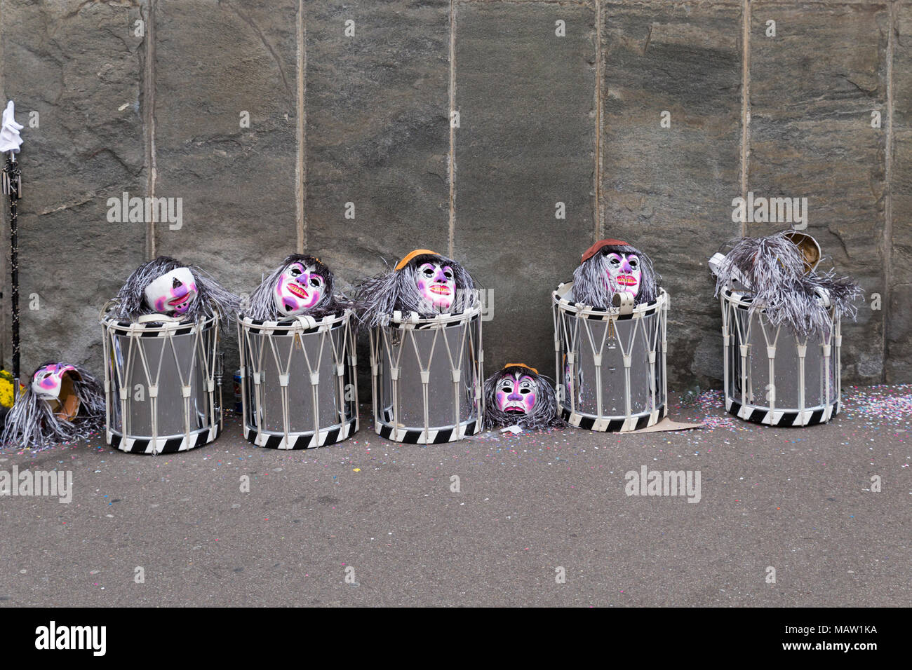 Basel carnival. Spiegelgasse, Basel, Switzerland - February 21st, 2018. Line of snare drums and masks in front of a gray wall - Stock Image