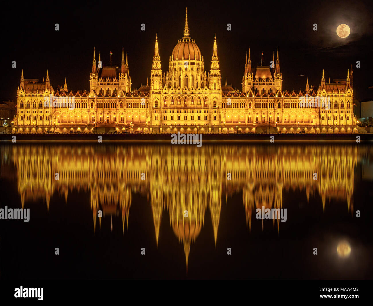 Hungarian Parliament Building (Budapest) at night reflected in water of Danube River and with full Moon above it - Stock Image