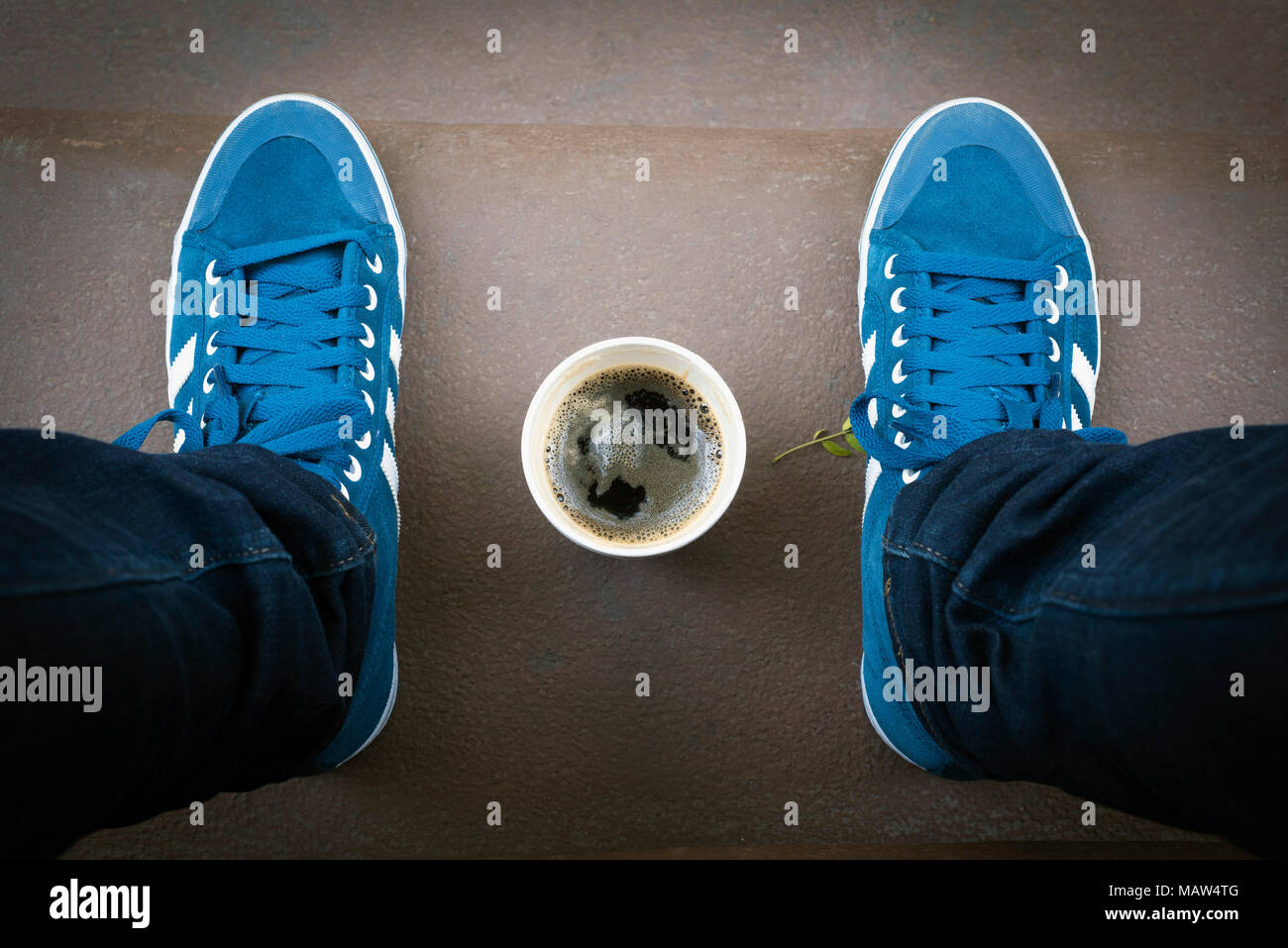 A cup of coffee between two feet. - Stock Image