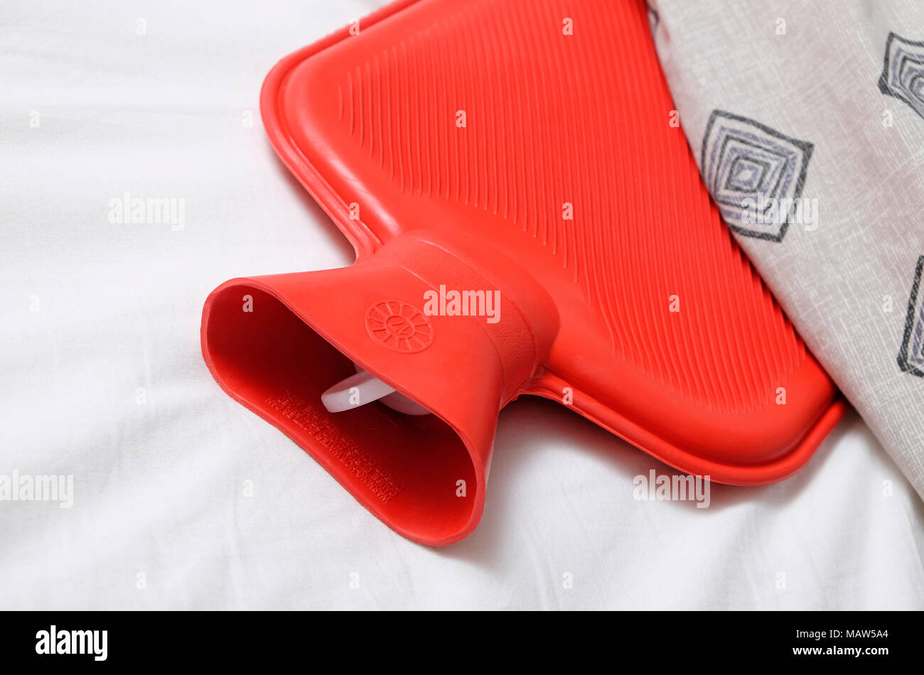 red hot water bottle in bed - Stock Image
