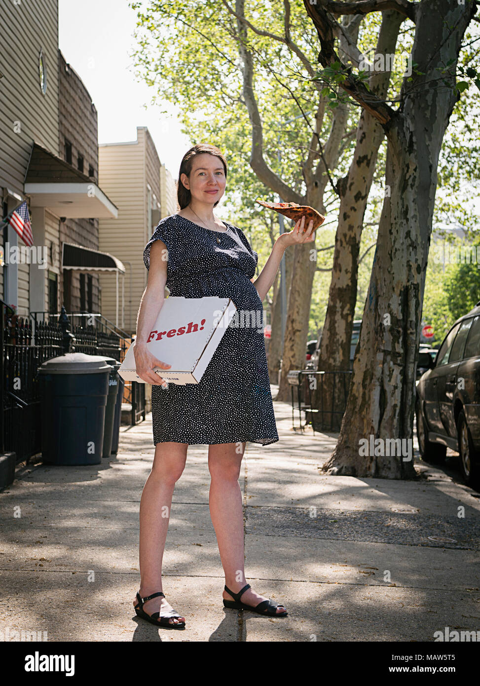 A pregnant woman standing on the street eating pizza. - Stock Image