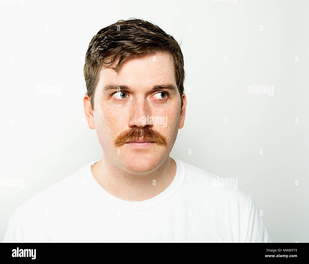 A man with freckles side eyeing. - Stock Image