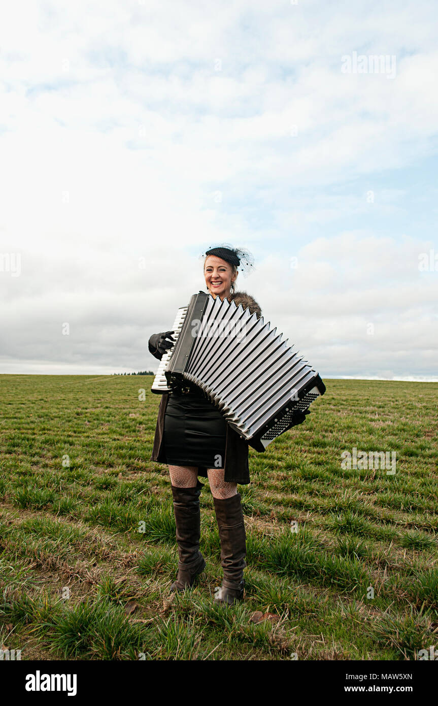 A woman playing an accordian in a field. - Stock Image