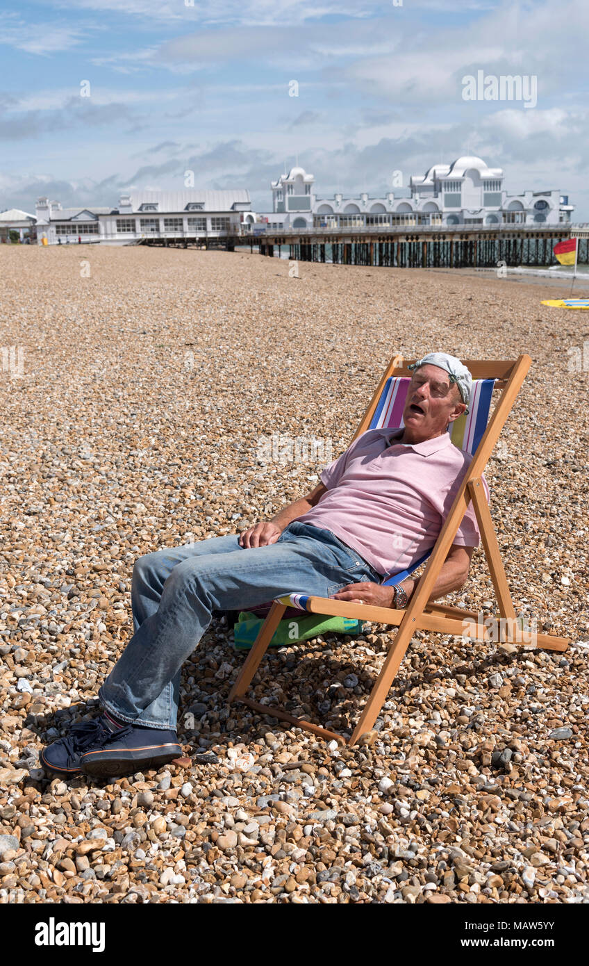 Elderly man wearing a knotted handkerchief on his head relaxing on the beach. Southsea, England UK - Stock Image