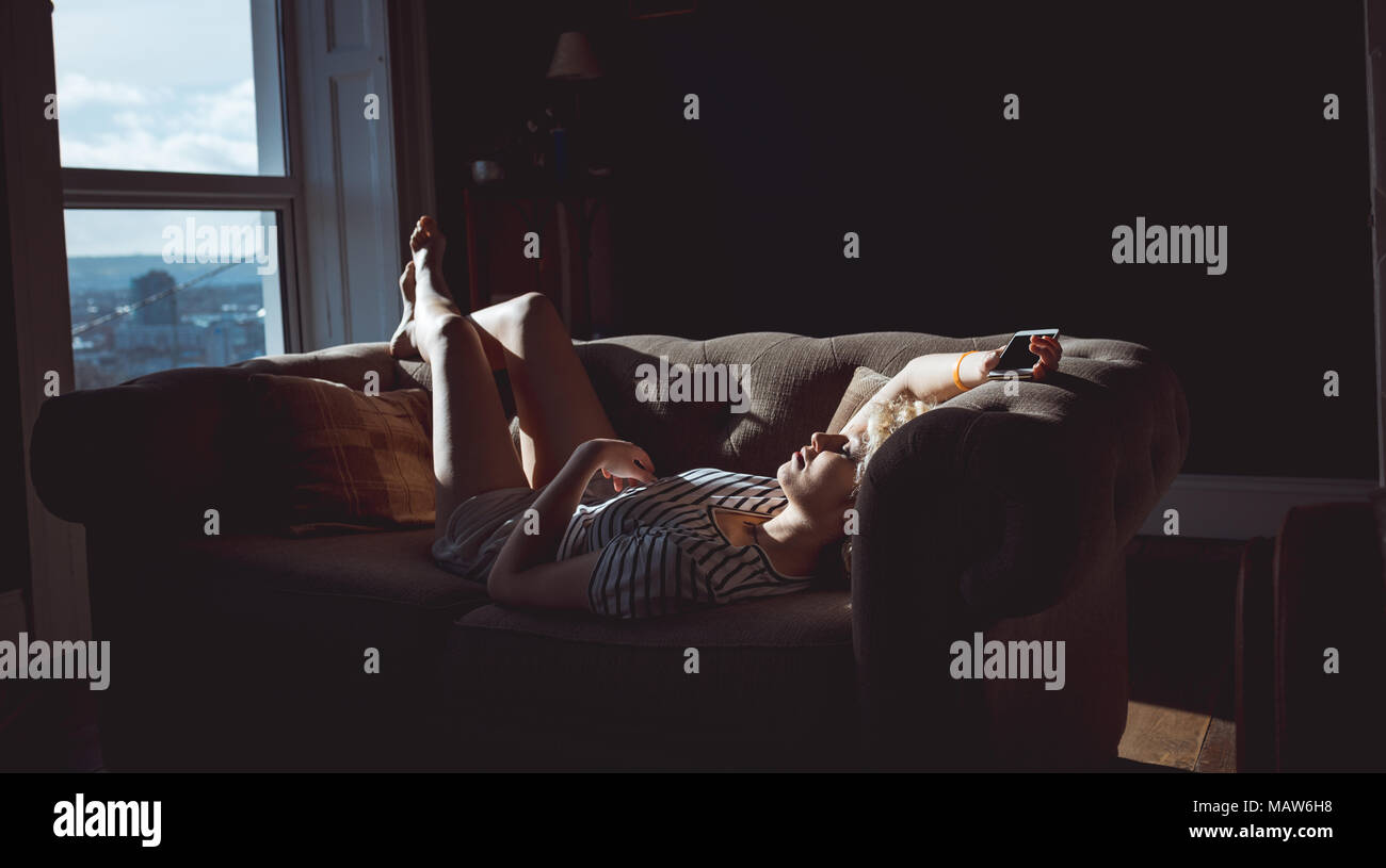 Woman sleeping in living room - Stock Image