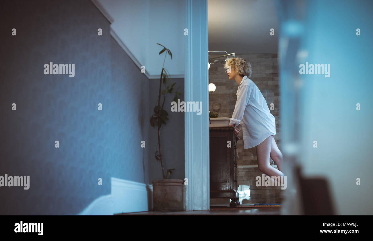 Woman standing in bathroom at home - Stock Image