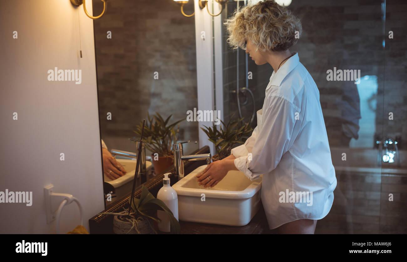 Woman washing her hand in bathroom - Stock Image
