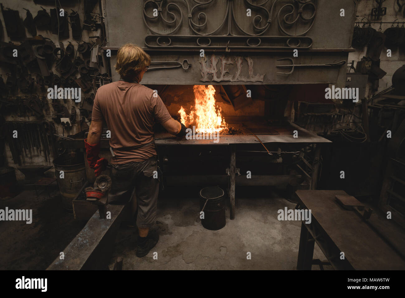 Blacksmith heating metal rod in fire - Stock Image