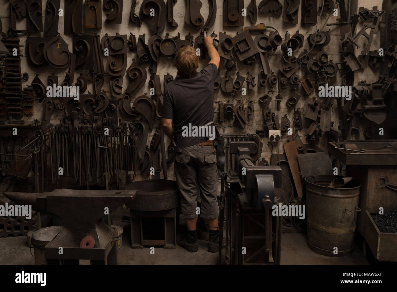 Blacksmith looking at metal equipments - Stock Image
