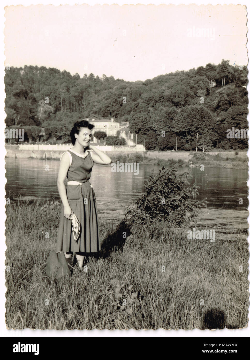 Lifestyle in the 50ies: a young woman stands near a river, France - Stock Image