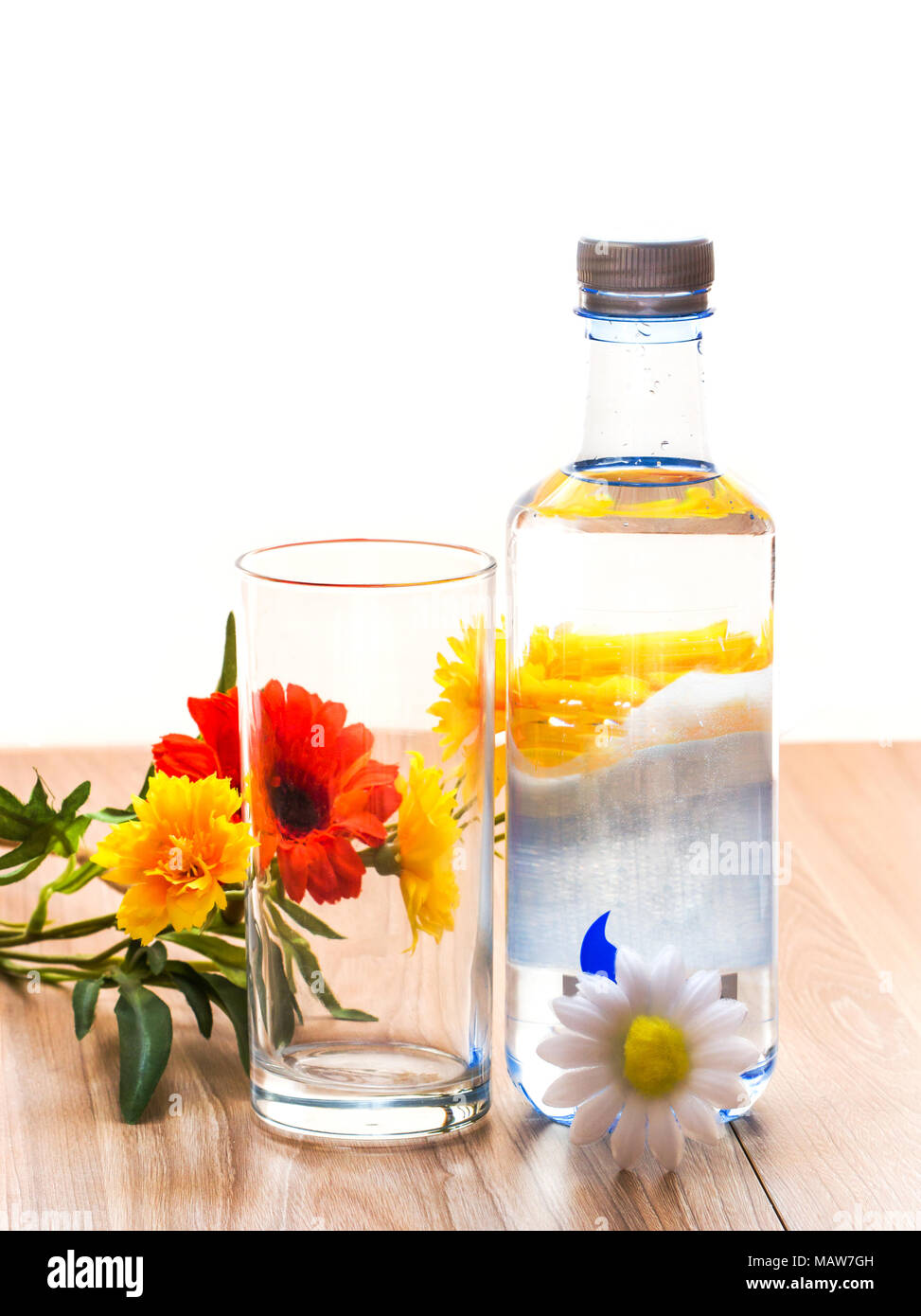 Water bottle mineral and glass of water and colorful flowers on wood table in bright day in concept drinking healthy, health care background - Stock Image