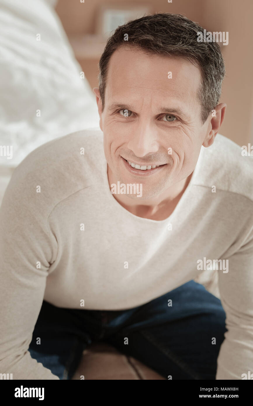 Satisfied pleasant man sitting and smiling. Stock Photo