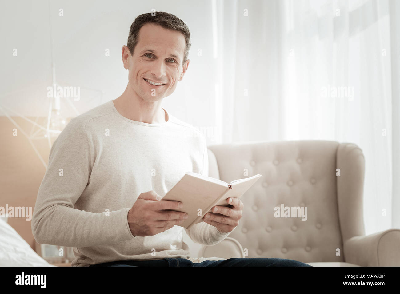 Satisfied smart man holding a book and smiling. Stock Photo