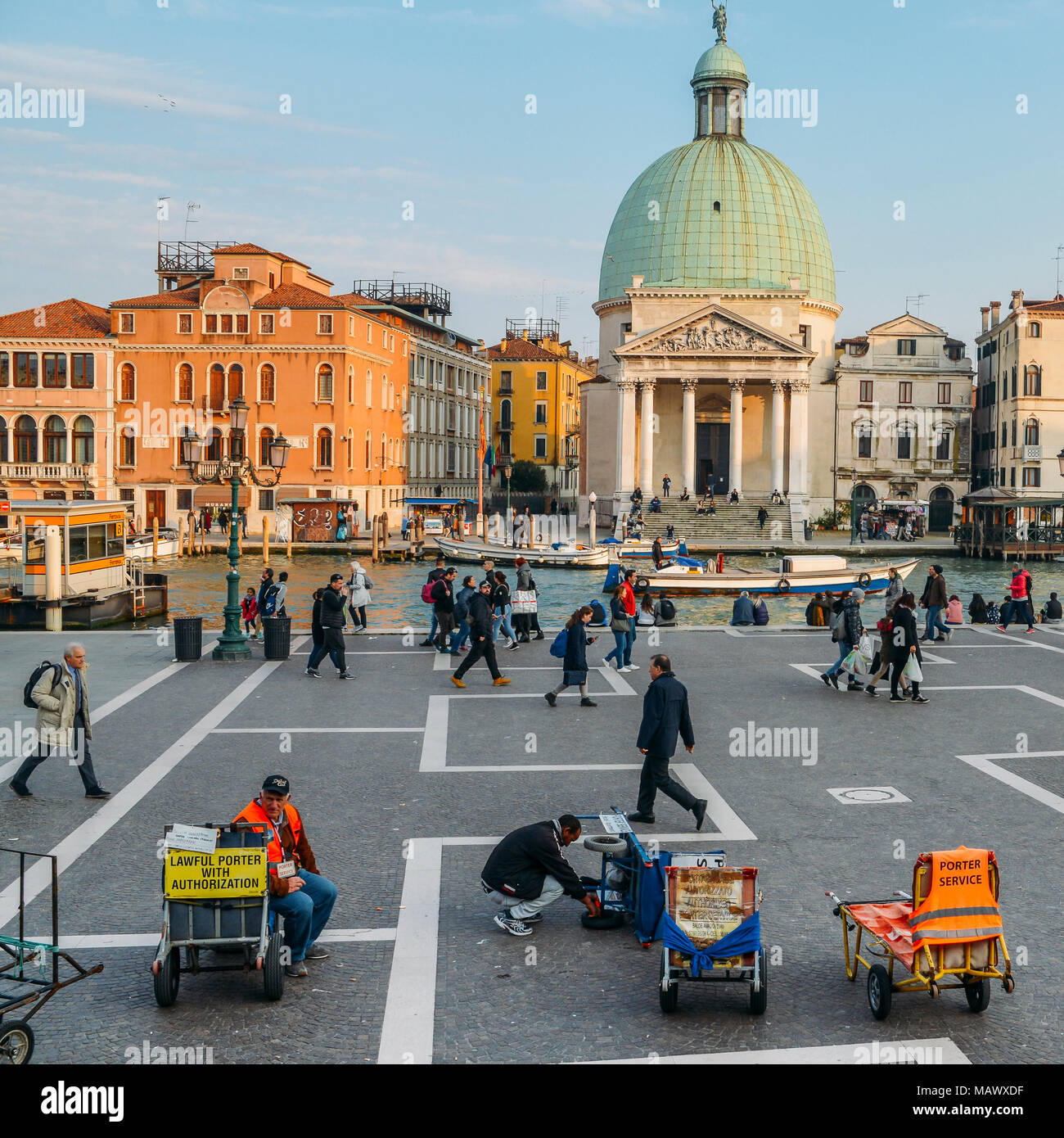 Luggage porters advertising their services in front of Venice's Santa Lucia railway station - Stock Image