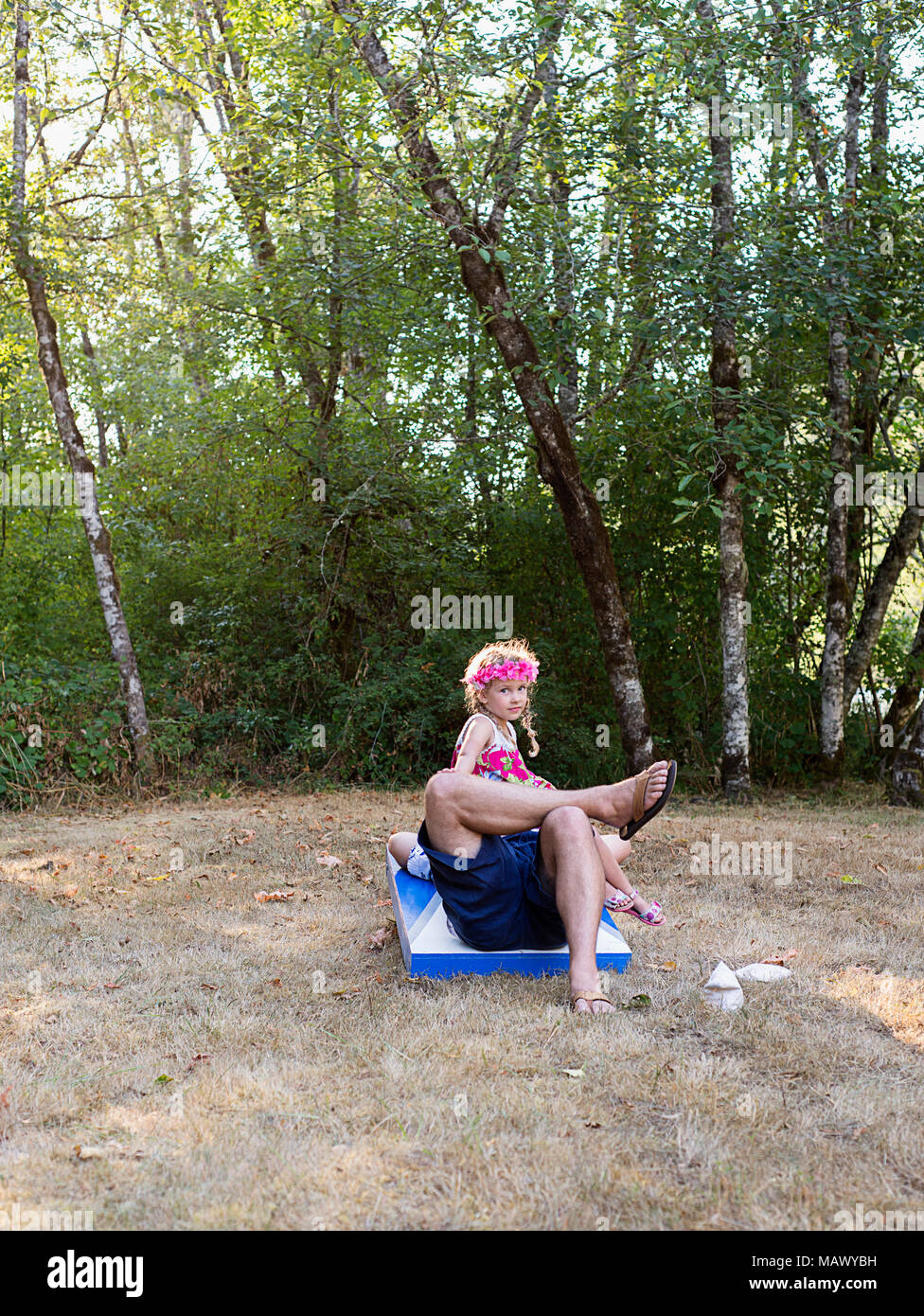 A young girl sitting on her dad. - Stock Image