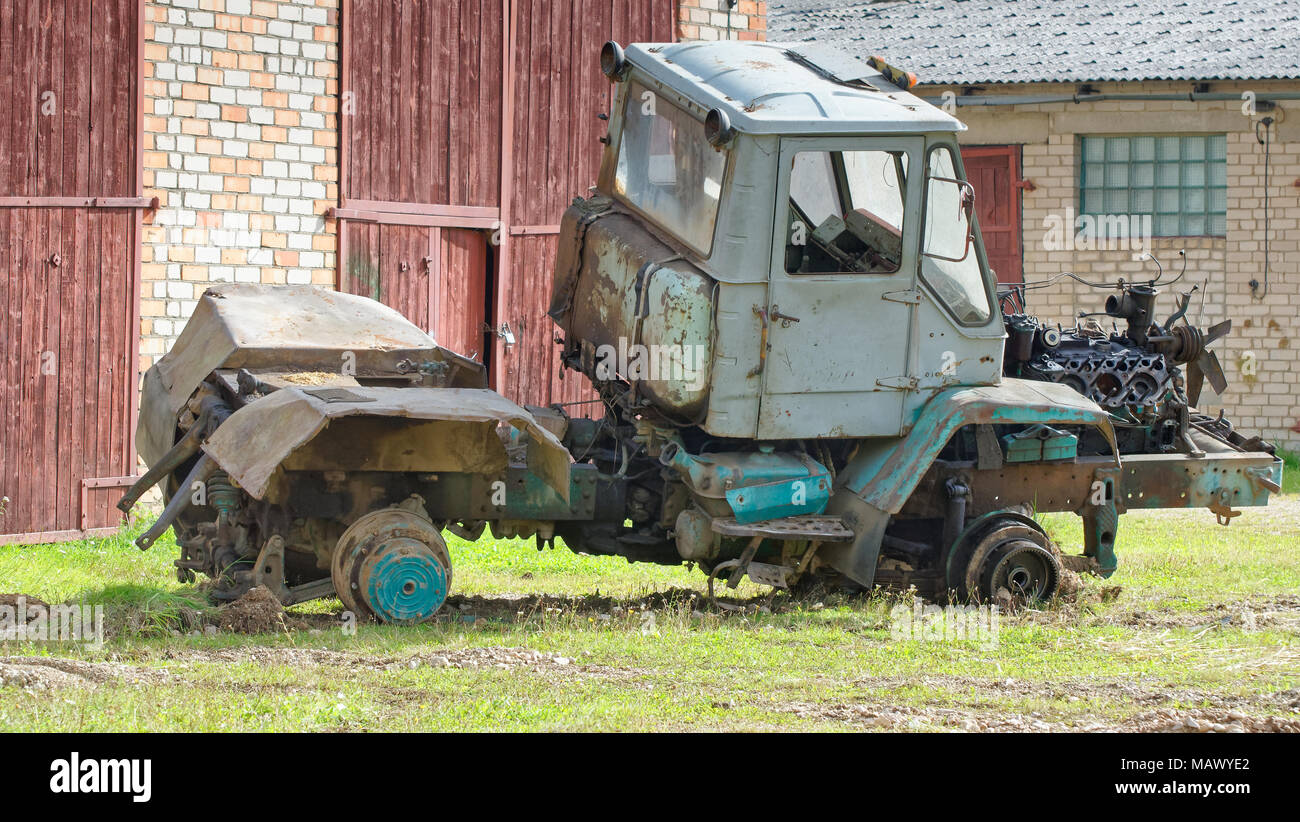 Side view of old disassembled tractor with engine with detached cylinder head and visible pistons Stock Photo
