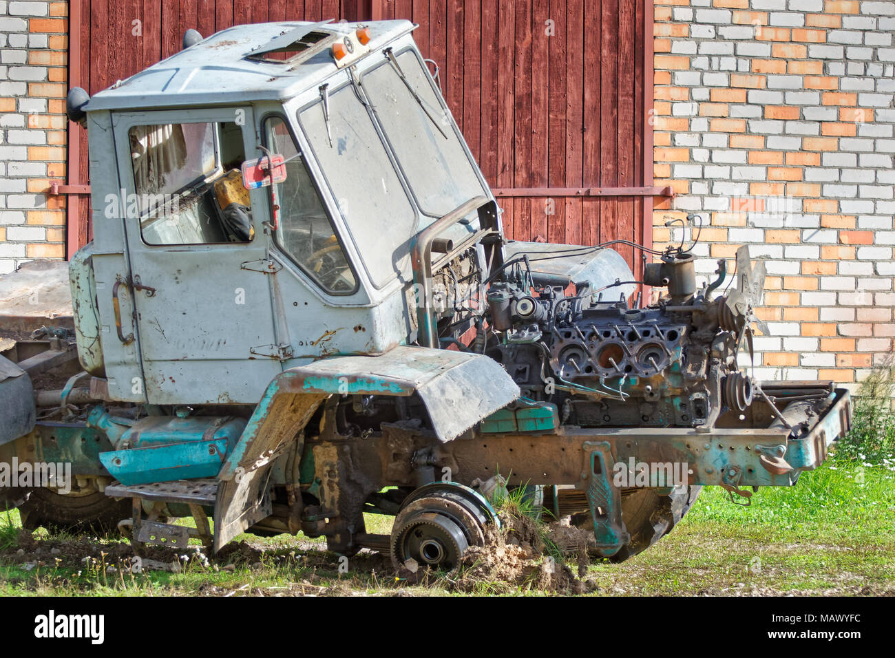Old disassembled tractor with removed engine compartment hood and dismantled engine Stock Photo