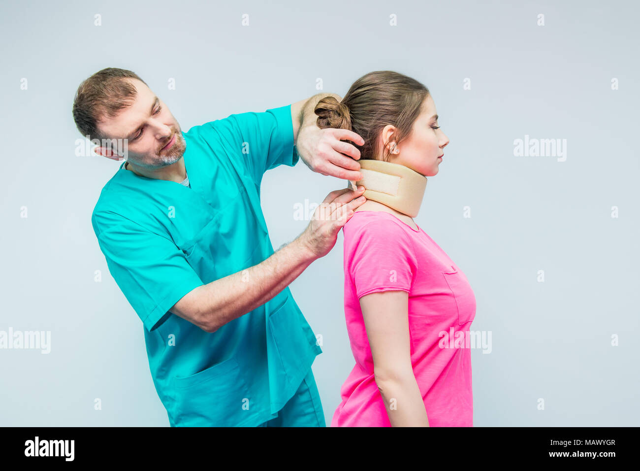 Neurologist doctor, therapist puts on young female patient neck injury, osteochondrosis collar to prevent and physiotherapy. Pain treatment. Neurology - Stock Image