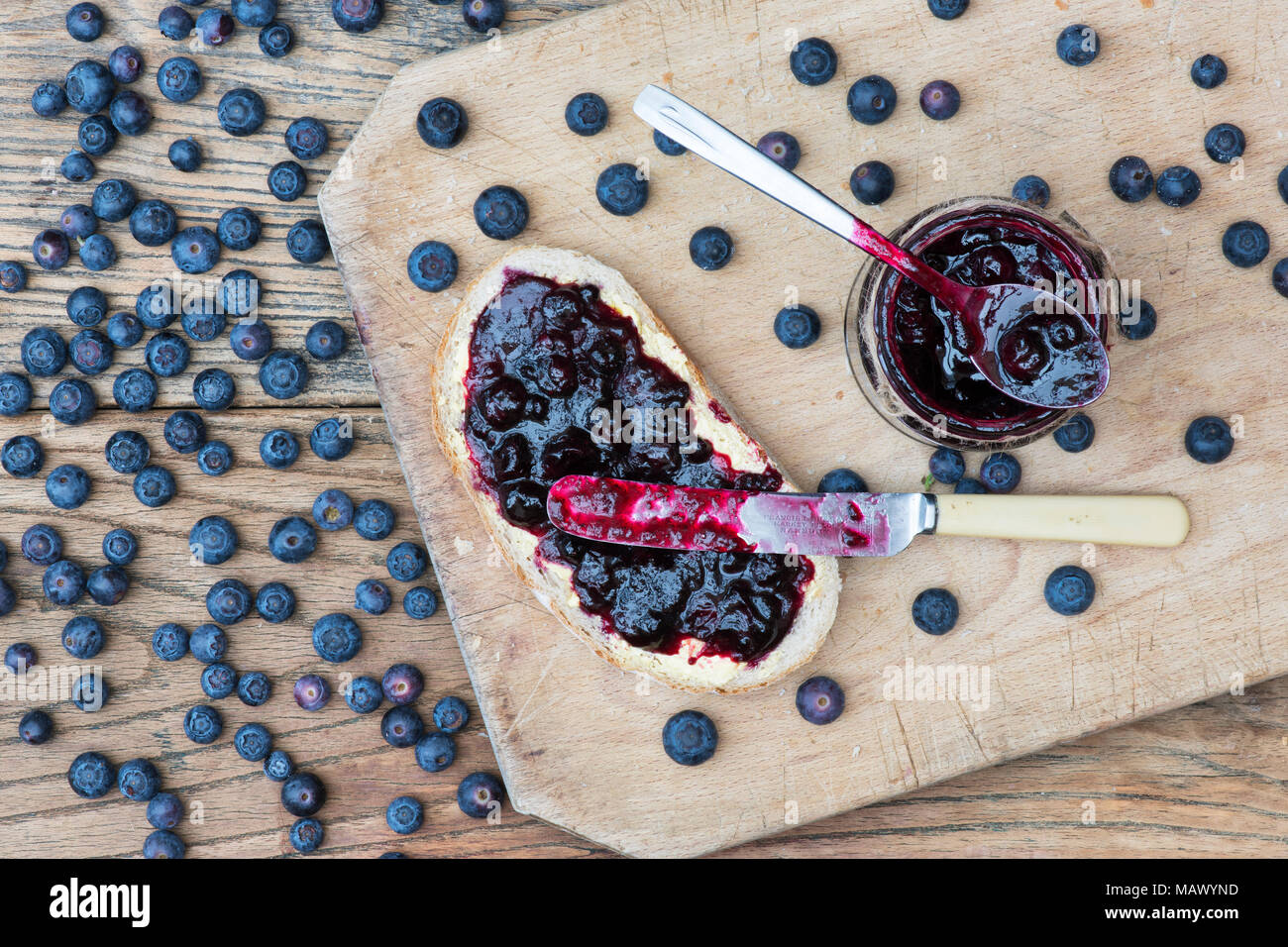 Homemade Blueberry jam and bread on a wood background - Stock Image