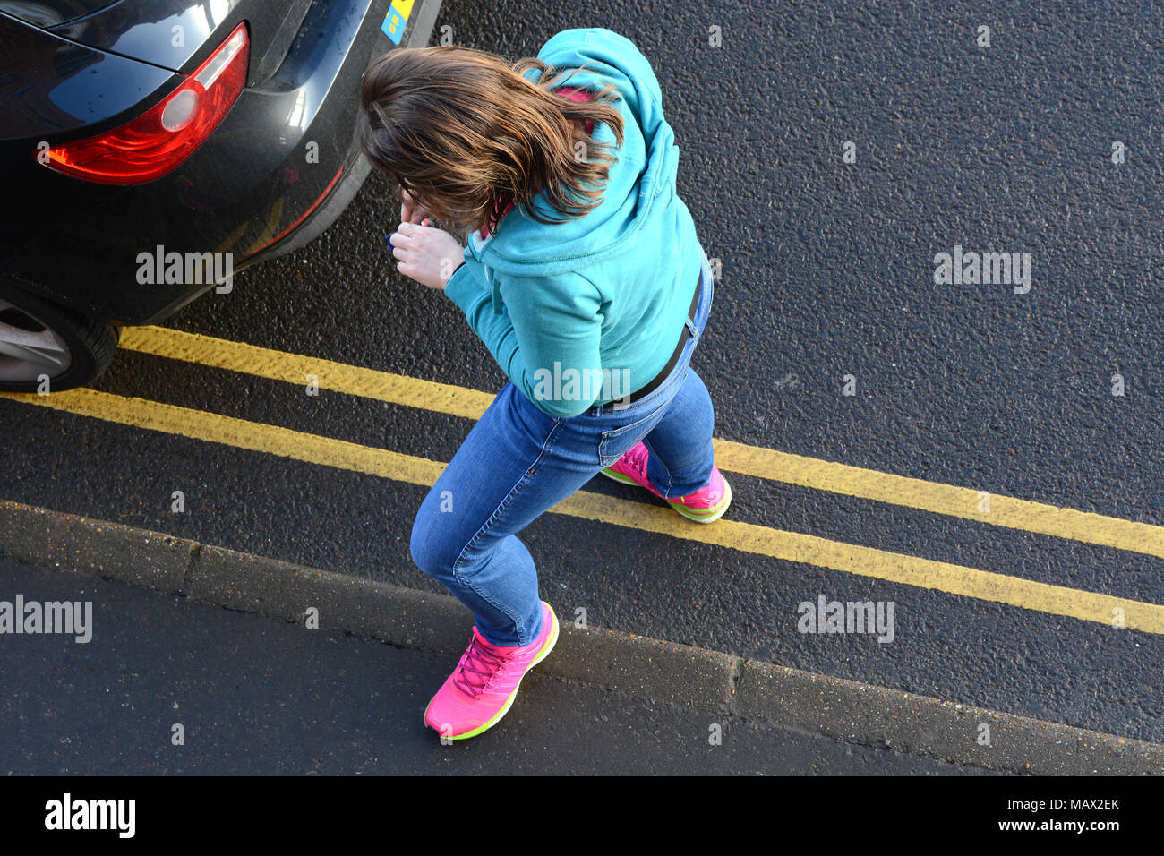 Girl in denim jeans and pink trainers standing still in the street - Stock Image
