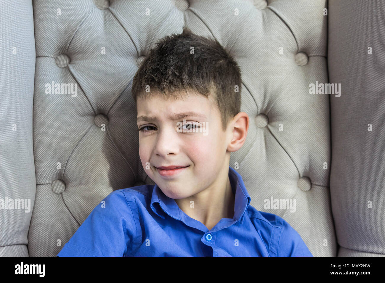 The disgruntled teen boy sitting at home - Stock Image