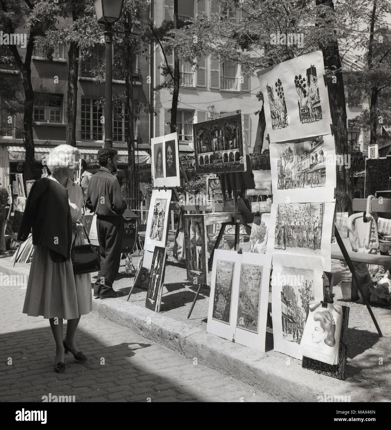 1950s historical picture showing paintings and artwork on sale on the place du tertre
