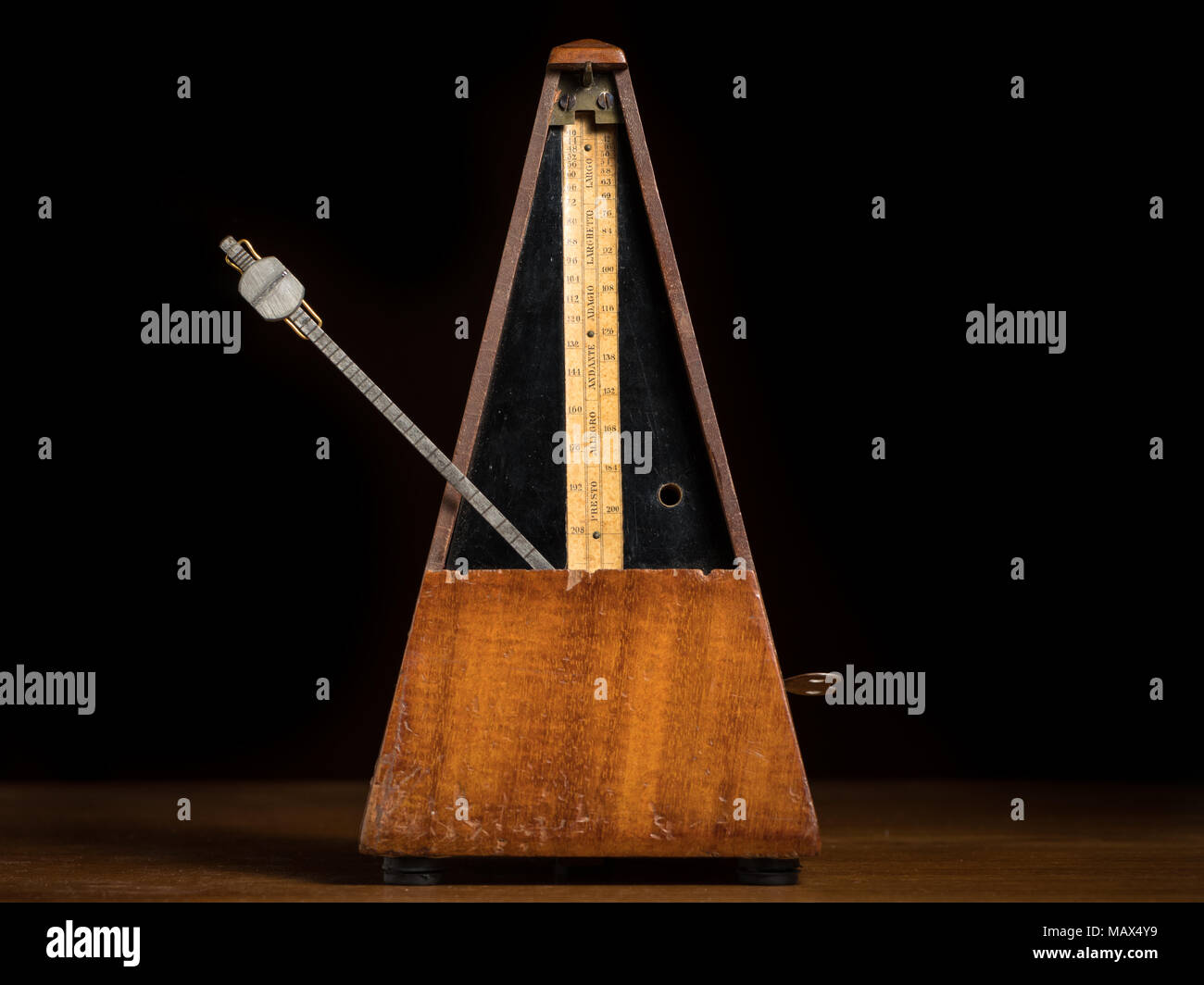 Detail of an old mechanic musical metronome, scale showing the various tempos, pendulum left - Stock Image