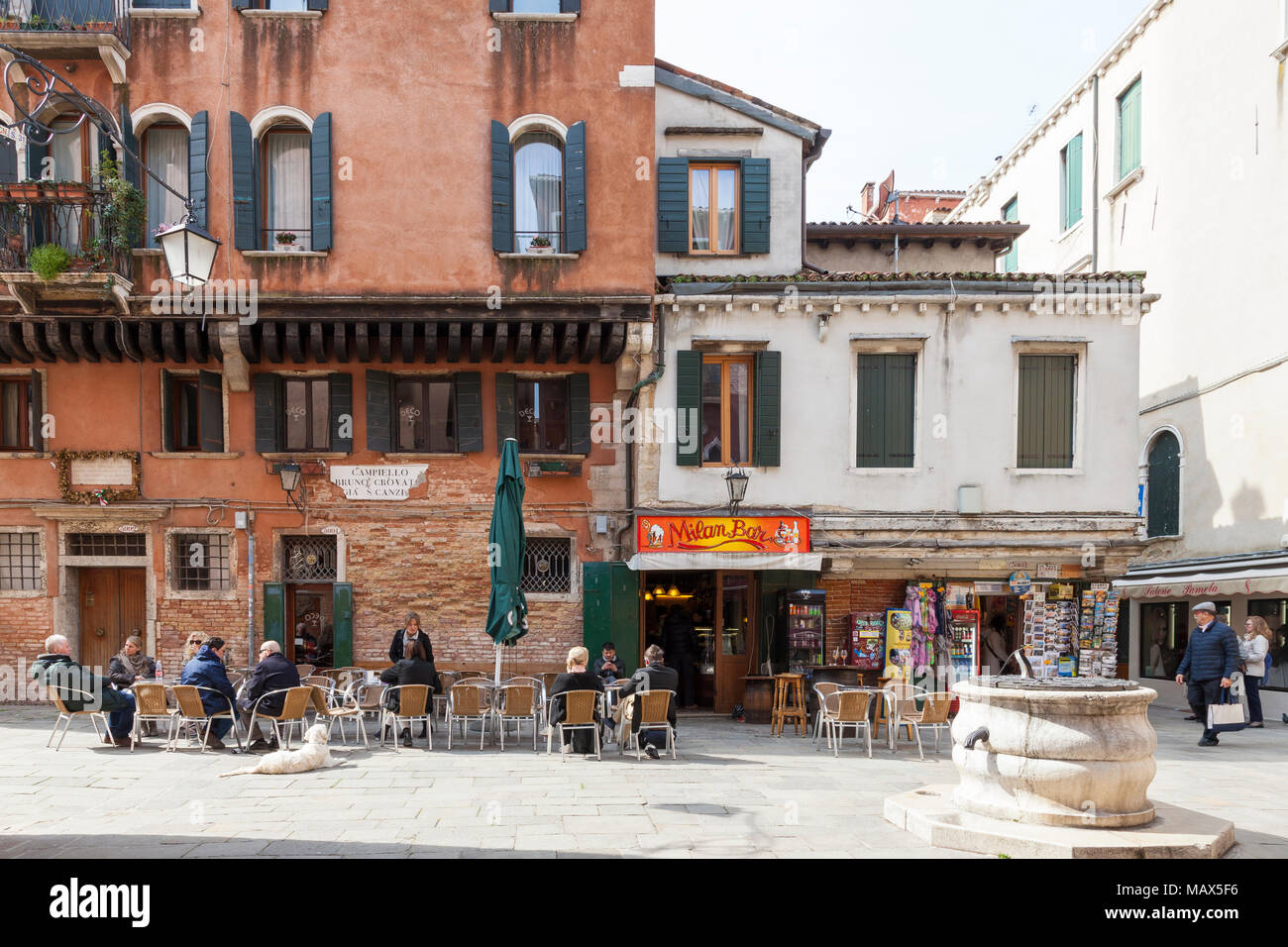 Local Venetians and tourists drinking outside the popular Milan Bar, Cannaregio, Venice, Italy  with a pozzo or ancient well in the foreground - Stock Image