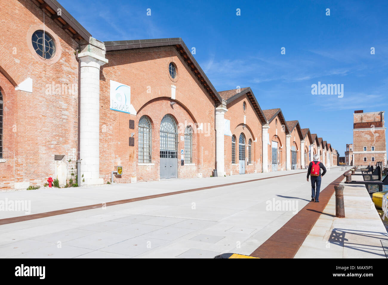 Man walking along the quay at Darsena Nuovissima, Arsenale, Venice, Italy passing the old boatbuilding workshops now used by Biennale and businesses - Stock Image