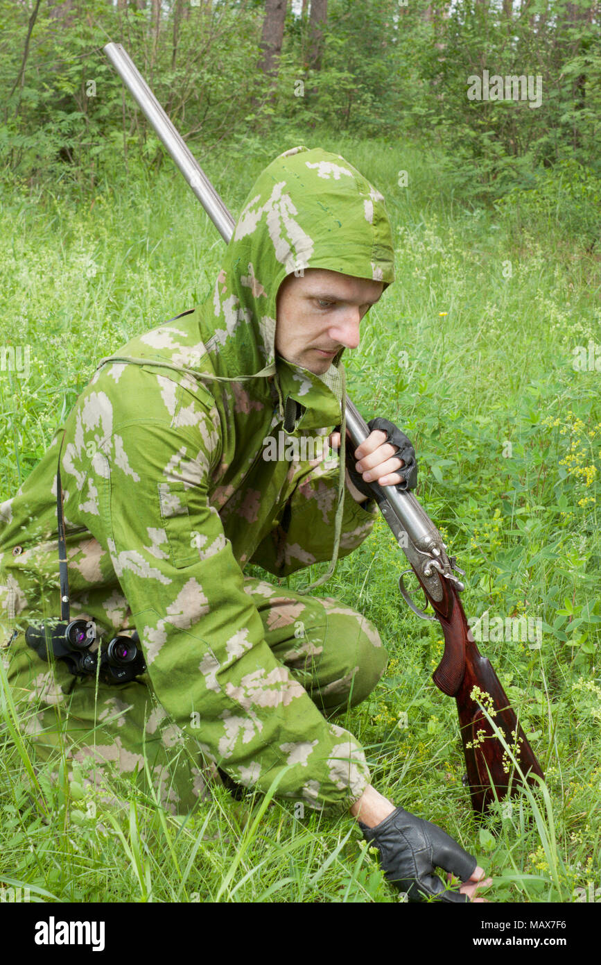 Hunter with an old rifle is considering the trail in a grass Stock Photo